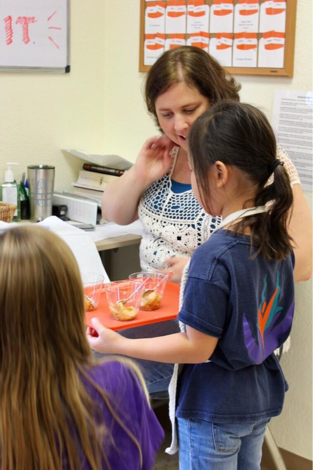 Student shows teacher her work displayed on a tray