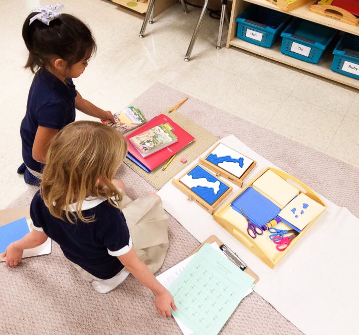 Two students sit on floor working together on a Montessori material