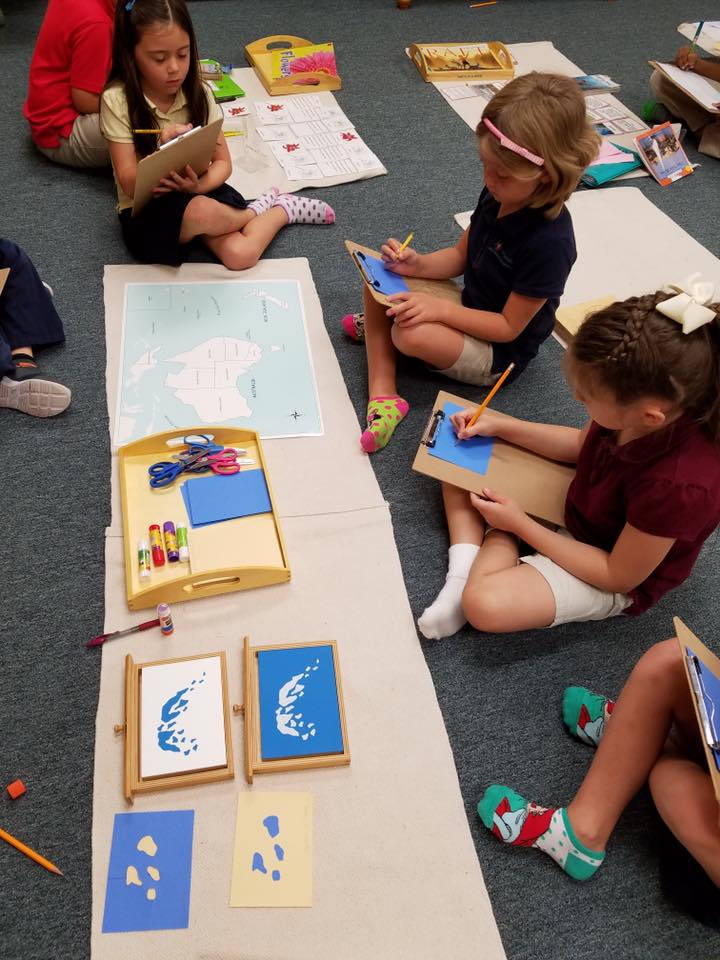 Students sitting on the floor around a Montessori work, taking notes
